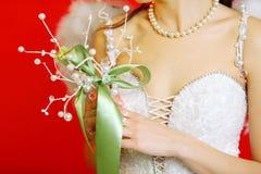 As mãos da noiva que desgastam no vestido prendem o ramalhete fotos de stock