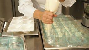 As mãos da pastelaria nas luvas brancas puseram o creme branco do chantiliy sobre o bolo do tiramisu video estoque