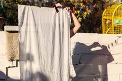 As mãos da roupa de suspensão da mulher bonita para secar após a lavanderia imagens de stock