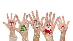As mãos das crianças aumentaram acima com símbolos pintados do Natal - Santa, boneco de neve, caixa atual, árvore de Natal e rena video estoque