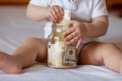 As mãos das crianças com dinheiro no frasco de vidro Imagens de Stock