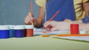 As mãos das crianças com escovas pintam com aquarelas filme