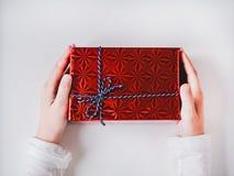 As mãos das crianças com um presente para pais imagem de stock royalty free
