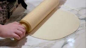 As mãos das crianças desenrolam o pino do rolo da massa da pizza na tabela vídeos de arquivo