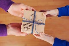 As mãos das crianças e as mãos do paizinho que guardam um presente ou uma caixa atual com papel de embalagem e etiqueta amarrada  Foto de Stock Royalty Free