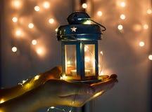 As mãos das crianças guardam a lanterna do Natal nas mãos no fundo do bokeh das luzes foto de stock royalty free