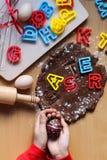 As m?os das crian?as guardam um ovo da p?scoa decorado Cozinhando biscoitos tradicionais da P?scoa Ovos da p?scoa Conceito do ali foto de stock royalty free