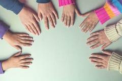 As mãos das crianças juntam-se junto na tabela Fotografia de Stock