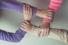 As mãos das crianças juntam-se junto na tabela Fotos de Stock