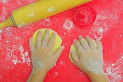 As mãos das crianças na farinha e na massa fotos de stock royalty free