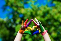 As mãos das crianças pintadas em cores brilhantes fazem uma forma do coração no fundo da natureza do verão Fotografia de Stock Royalty Free