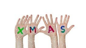 As mãos das crianças que aumentam acima com símbolos pintados do Natal filme