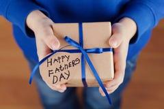 As mãos das crianças que guardam um presente ou uma caixa atual com papel de embalagem e etiqueta amarrada da fita azul no dia de Fotografia de Stock