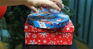 As mãos das crianças tomam bolas do Natal de uma caixa festiva vídeos de arquivo