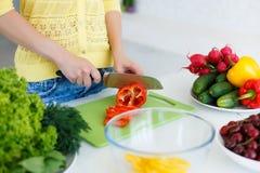 As mãos das donas de casa durante o cozimento da salada Foto de Stock