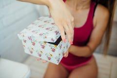 As mãos das mulheres abrem uma caixa Imagem de Stock
