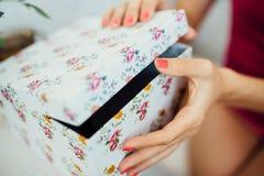 As mãos das mulheres abrem uma caixa Foto de Stock