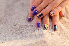As mãos das mulheres bonitas com um tratamento de mãos profissional na areia Fotografia de Stock