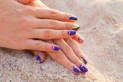 As mãos das mulheres bonitas com um tratamento de mãos profissional na areia Imagem de Stock