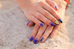 As mãos das mulheres bonitas com um tratamento de mãos profissional na areia Fotografia de Stock Royalty Free