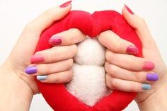 As mãos das mulheres com pregos coloridos Imagens de Stock