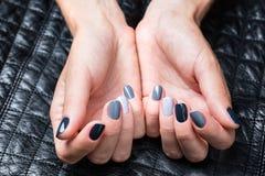 As mãos das mulheres com um tratamento de mãos à moda Fotos de Stock