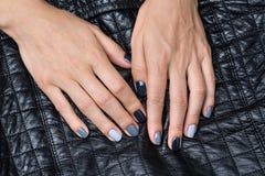 As mãos das mulheres com um tratamento de mãos à moda Imagem de Stock Royalty Free