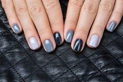 As mãos das mulheres com um tratamento de mãos à moda Imagens de Stock