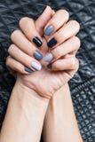 As mãos das mulheres com um tratamento de mãos à moda Fotos de Stock Royalty Free