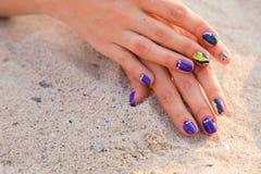 As mãos das mulheres com um tratamento de mãos agradável na areia Imagens de Stock Royalty Free