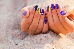 As mãos das mulheres com um tratamento de mãos agradável na areia Fotografia de Stock Royalty Free