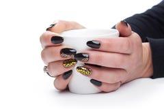 As mãos das mulheres com um tratamento de mãos e um copo agradáveis Isolado nos vagabundos brancos Fotos de Stock
