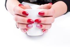 As mãos das mulheres com um tratamento de mãos e um copo agradáveis Isolado nos vagabundos brancos Foto de Stock