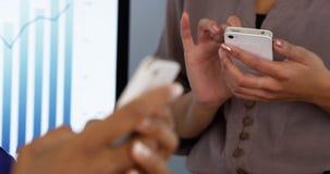 As mãos das mulheres das mulheres de negócios que trabalham em telefones celulares Imagens de Stock
