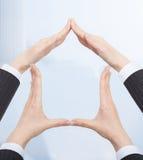 As mãos das mulheres de negócios que formam a estrutura da casa Imagens de Stock