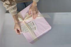 As mãos das mulheres em uma mentira clara da camiseta em uma caixa de presente cor-de-rosa grande bonita, envolvida em uma fita b foto de stock