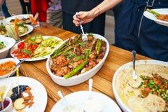 As mãos das mulheres empilham-se uma refeição em uma placa do almoço O conceito da nutrição bufete Alimento jantar O conceito da  Foto de Stock