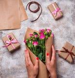 As mãos das mulheres envolvem um ramalhete das rosas no papel Imagens de Stock Royalty Free