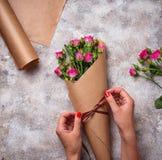 As mãos das mulheres envolvem um ramalhete das rosas no papel Imagem de Stock