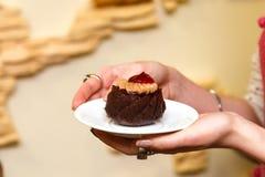 As mãos das mulheres guardam uma pastelaria em uma placa Fotografia de Stock