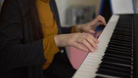 As mãos das mulheres jogam no sintetizador eletrônico filme