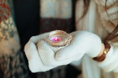 As mãos das mulheres protegem a luz de vela, em uma luva branca foto de stock