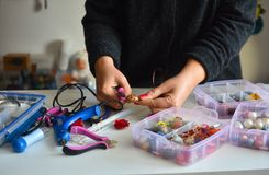As mãos das mulheres que fazem a joia bonita fotografia de stock royalty free