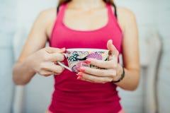 As mãos das mulheres que guardam um copo colorido do chá Imagens de Stock