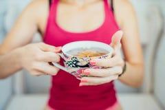 As mãos das mulheres que guardam um copo colorido do chá Imagens de Stock Royalty Free