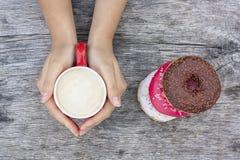 As mãos das mulheres que guardam uma xícara de café com anéis de espuma Fotografia de Stock