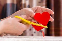 As mãos das mulheres que scissoring para fora o coração de papel para o dia de Valentim Imagens de Stock Royalty Free