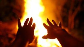 As mãos das mulheres são tiradas para atear fogo A menina é aquecida pela fogueira na floresta durante o piquenique vídeos de arquivo
