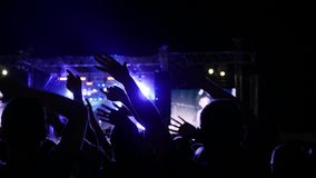 As mãos de balanço no festival de música, braços da audiência entusiasmado aumentaram dos povos em luzes brilhantes no festival d video estoque