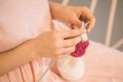 As mãos de confecção de malhas bonitas do ` s das mulheres, rosa relaxado coloriram o passatempo do humor meditação agradável do  foto de stock